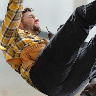 homme qui tombe sur le sol à côté d'un panneau sol glissant