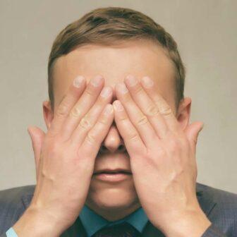 homme qui se cache les yeux avec ses mains