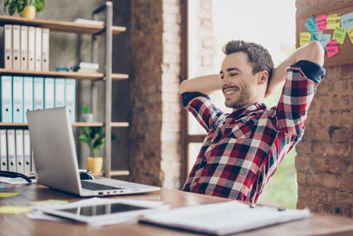 jeune homme souriant les bras croisés derrière la tête assis à son bureau derrière un ordinateur portable