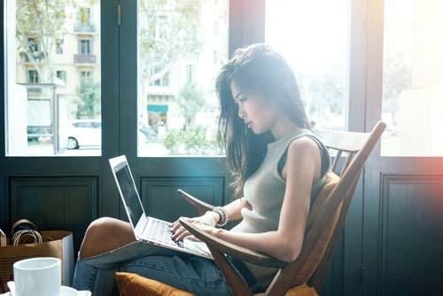 femme asiatique assise sur une chaise devant son ordinateur portable